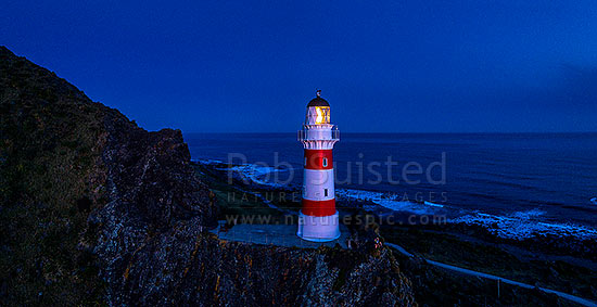 Cape Palliser Lighthouse shining out from the southern most tip of the North Island (Matakitakiakupe). Aerial panorama after dark, Cape Palliser, South Wairarapa District, Wellington Region, New Zealand (NZ) stock photo.