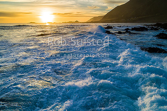 Waves crashing into Cape Palliser (Matakitakiakupe) rocky coastline at dusk, Cape Palliser, South Wairarapa District, Wellington Region, New Zealand (NZ) stock photo.