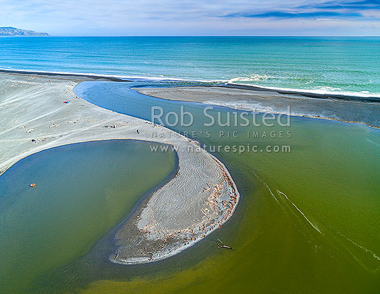 Lake Ferry (Onoke) outlet draining the Ruamahanga River into Palliser Bay. Cape Palliser far left. Aerial view, Lake Ferry, South Wairarapa District, Wellington Region, New Zealand (NZ) stock photo.