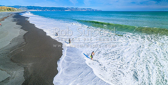Fishermen surfcasting on Whangaimoana Beach, Palliser bay. Cape Palliser beyond. Aerial panorama, Lake Ferry, South Wairarapa District, Wellington Region, New Zealand (NZ) stock photo.