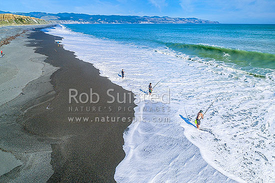 Fishermen surfcasting on Whangaimoana Beach, Palliser bay. Cape Palliser beyond. Aerial view, Lake Ferry, South Wairarapa District, Wellington Region, New Zealand (NZ) stock photo.