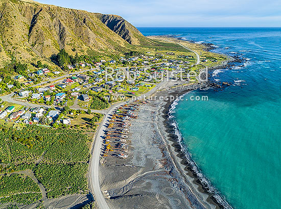 Ngawi small village on Palliser Bay, uses bulldozers lining the beach to launch fishing vessels. Aerial view of small coastal settlement, Ngawi, South Wairarapa District, Wellington Region, New Zealand (NZ) stock photo.