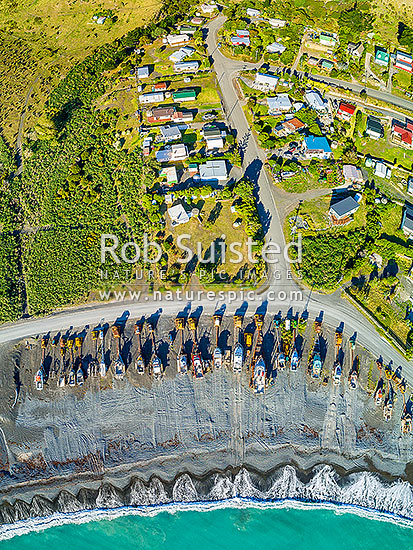 Ngawi small village on Palliser Bay, uses bulldozers lining the beach to launch fishing vessels. Aerial view from above of fishing boats, Ngawi, South Wairarapa District, Wellington Region, New Zealand (NZ) stock photo.