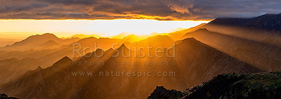 Dramatic sunrise over Awatere Valley (far left). Crepuscular rays lighting the Hodder River Valley, Camden and Gladstone Downs Stations. Panorama, Awatere Valley, Marlborough District, Marlborough Region, New Zealand (NZ) stock photo.