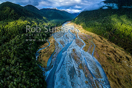 Maruia River flats draining down from Lewis Pass, in breaking weather. Aerial view of braided river flats and beech forest. Mt Mueller (1630m) and Freyberg Range at left, Maruia Springs, Buller District, West Coast Region, New Zealand (NZ) stock photo.