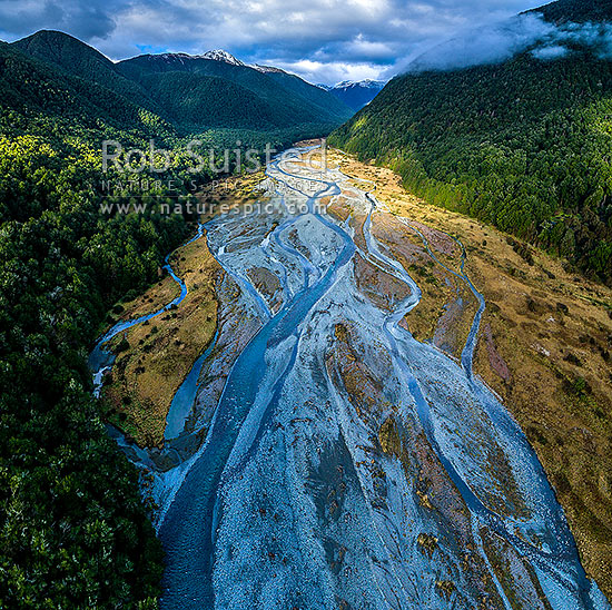 Maruia River flats draining down from Lewis Pass, in breaking weather. Aerial view of braided river flats and beech forest. Mt Mueller (1630m) and Freyberg Range at left. Square format, Maruia Springs, Buller District, West Coast Region, New Zealand (NZ) stock photo.
