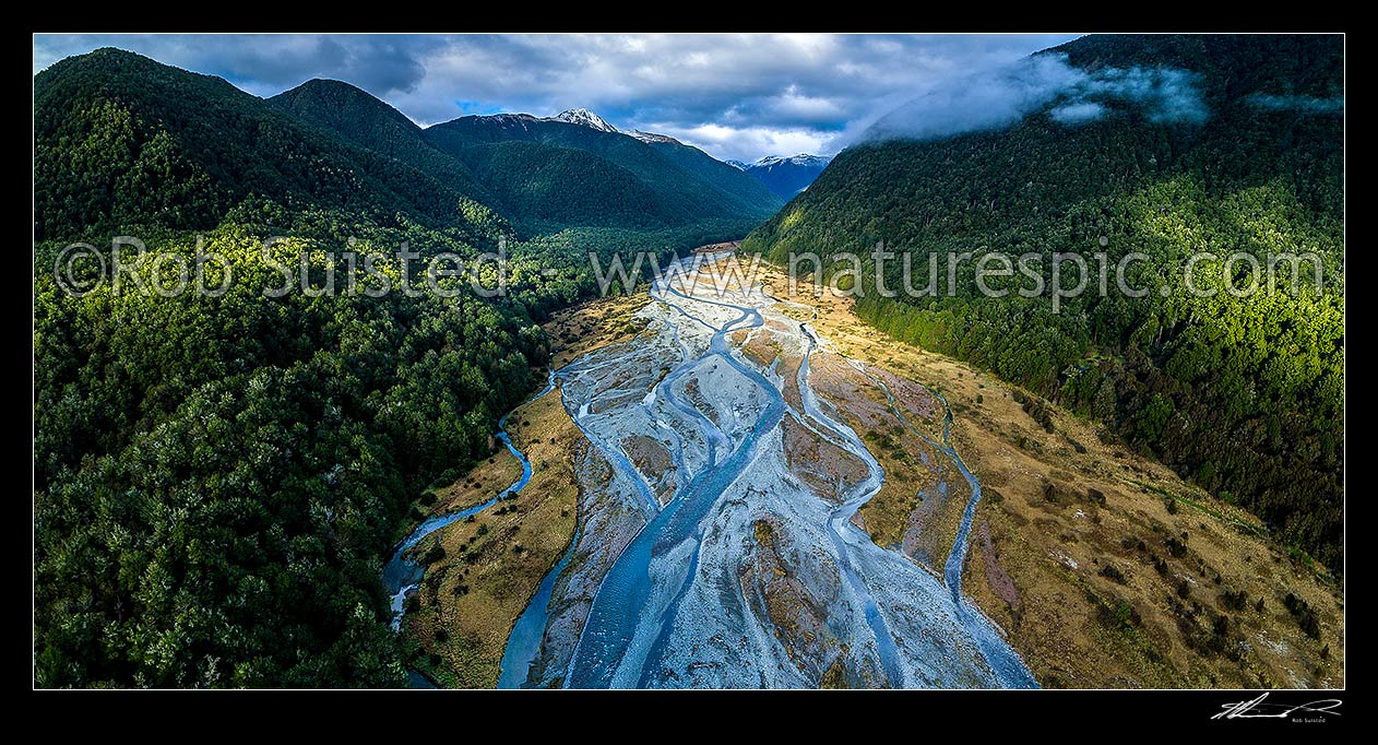Image of Maruia River flats below Lewis Pass, in breaking weather. Aerial view of braided river flats and beech forest. Mt Mueller (1630m) and Freyberg Range at left, Opera Range and Spenser Mountains distant. Panorama, Maruia Springs, Buller District, West Coast Region, New Zealand (NZ) stock photo image