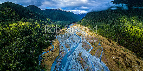 Maruia River flats below Lewis Pass, in breaking weather. Aerial view of braided river flats and beech forest. Mt Mueller (1630m) and Freyberg Range at left, Opera Range and Spenser Mountains distant. Panorama, Maruia Springs, Buller District, West Coast Region, New Zealand (NZ) stock photo.