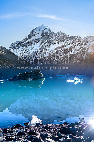 Aoraki / Mount Cook (3754m) above Hooker Lake and Hooker Glacier. Glacial rock flour creates a dramatic blue hue to the waters of Hooker Lake, Aoraki / Mount Cook National Park, MacKenzie District, Canterbury Region, New Zealand (NZ) stock photo.