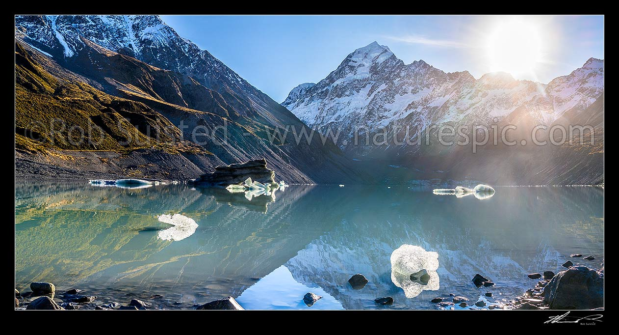 Image of Aoraki / Mount Cook (3754m) above Hooker Glacier and Hooker Lake with floating ice. Sun rising over the Mt Cook Range. Panorama, Aoraki / Mount Cook National Park, MacKenzie District, Canterbury Region, New Zealand (NZ) stock photo image