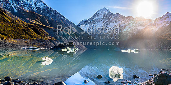 Aoraki / Mount Cook (3754m) above Hooker Glacier and Hooker Lake with floating ice. Sun rising over the Mt Cook Range. Panorama, Aoraki / Mount Cook National Park, MacKenzie District, Canterbury Region, New Zealand (NZ) stock photo.