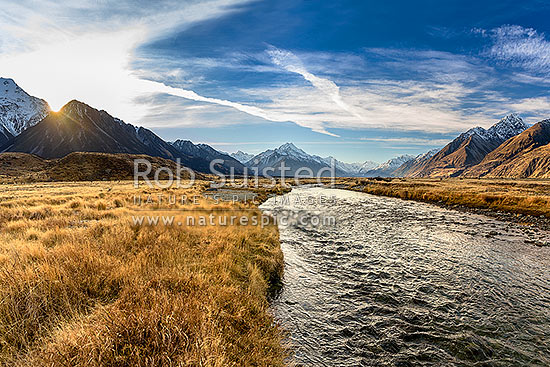 Tasman Valley sunset, with Aoraki Mt Cook (3754m) centre above clear mountain stream. Ben Ohau Range left, and Burnett Mountains right. Panorama, Aoraki / Mount Cook National Park, MacKenzie District, Canterbury Region, New Zealand (NZ) stock photo.