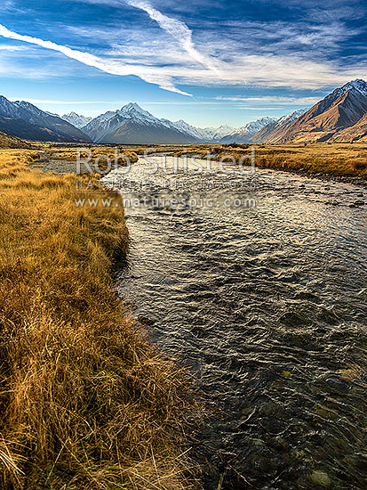 Aoraki Mount Cook in the Tasman River Valley. Ben Ohau Range at left, Burnett Mountains right. Clear mountain stream below, Aoraki / Mount Cook National Park, MacKenzie District, Canterbury Region, New Zealand (NZ) stock photo.