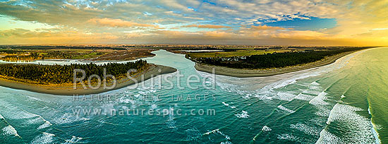 Waimakariri River mouth at sunrise. Brooklands Lagoon at left, Kairaki and The Pines Beach at right, Canterbury plains beyond. Aerial panorama, Kaiapoi, Waimakariri District, Canterbury Region, New Zealand (NZ) stock photo.