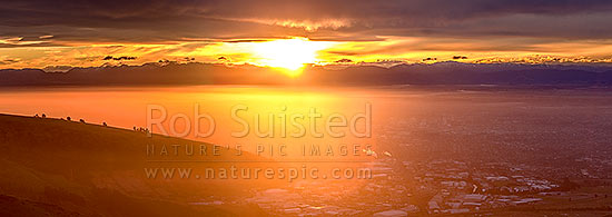 Sunset over Christchurch City. Sun setting behind the Southern Alps. Seen from The Port Hills. Panorama, Christchurch, Christchurch City District, Canterbury Region, New Zealand (NZ) stock photo.