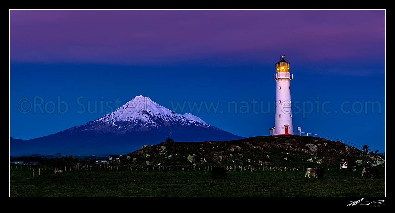 Image of Cape Egmont and lighthouse, with a snow cloaked Mt Taranaki behind. After dusk panorama, Cape Egmont, South Taranaki District, Taranaki Region, New Zealand (NZ) stock photo image