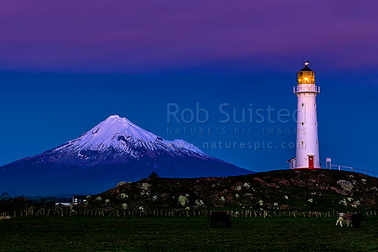 Cape Egmont and lighthouse, with a snow cloaked Mt Taranaki behind. After dusk, Cape Egmont, South Taranaki District, Taranaki Region, New Zealand (NZ) stock photo.