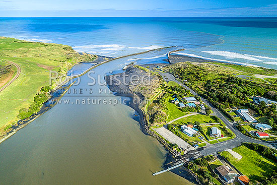 Patea River mouth, with training walls, breakwaters or moles visible.  Patea surf club, houses and boat ramp below.  South Taranaki Bight. Aerial view, Patea, South Taranaki District, Taranaki Region, New Zealand (NZ) stock photo.