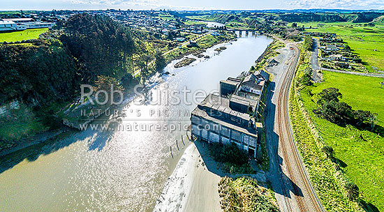 Patea River and Patea township, with remnants of the Patea freezing works, coolstores and wharves below. Marton - New Plymouth railway line right. Aerial view. Mt Taranaki distant, Patea, South Taranaki District, Taranaki Region, New Zealand (NZ) stock photo.