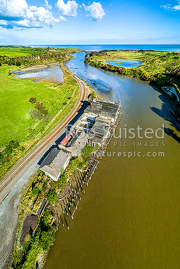 Patea River mouth, with remnants of the Patea freezing works, coolstores and wharves below. Marton - New Plymouth railway line left. Aerial view, Patea, South Taranaki District, Taranaki Region, New Zealand (NZ) stock photo.