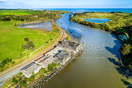 Patea River mouth, with remnants of the Patea freezing works, coolstores and wharves below. Marton - New Plymouth railway line left, Waioturi Marae beyond. Aerial view, Patea, South Taranaki District, Taranaki Region, New Zealand (NZ) stock photo.