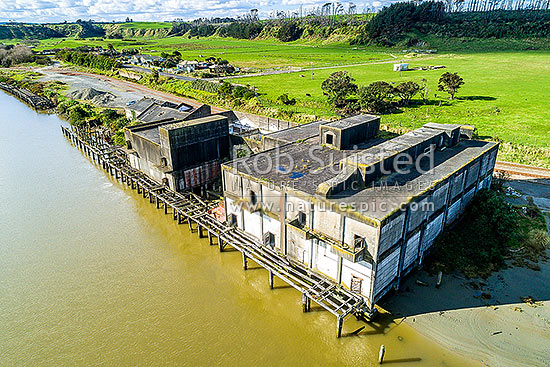 Patea River, with remnants of the Patea freezing works, coolstores and wharves. Remediated freezing works site, and Marton - New Plymouth railway line, behind. Aerial view, Patea, South Taranaki District, Taranaki Region, New Zealand (NZ) stock photo.