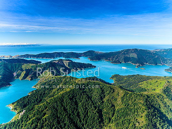 Tory Channel with Interislander Ferry passing Te Weuweu Bay, seen from above Cook's Lookout (low centre) on Arapawa Island. Umuwheke Bay left, Cook Strait and North Island beyond left. Aerial view, Marlborough Sounds, Marlborough District, Marlborough Region, New Zealand (NZ) stock photo.