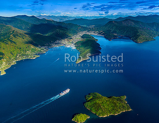Ferry sailing into Picton township. Waikawa Bay at left. The Snout centre. Snowy Inland Kaikoura Ranges beyond. Aerial view, Marlborough Sounds, Marlborough District, Marlborough Region, New Zealand (NZ) stock photo.