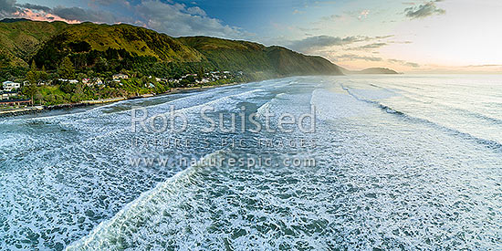 Paekakariki Beach (Whareroa Beach) and houses, with a heavy swell rolling in. Waireka Point in distance. Aerial panorama, Paekakariki, Kapiti Coast District, Wellington Region, New Zealand (NZ) stock photo.