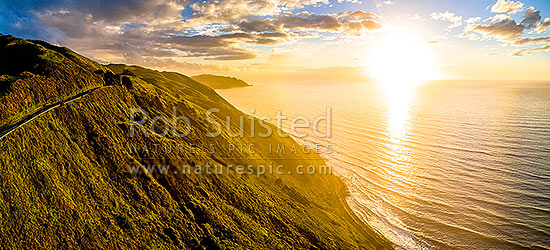 Paekakariki to Pukerua Bay SH1 road passing below the Paekakariki Hill Road. Sunset over Pukerua Bay coastline. Wairaka Point distant. Aerial panorama, Paekakariki, Kapiti Coast District, Wellington Region, New Zealand (NZ) stock photo.