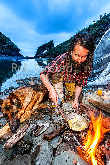 Leon Dalziel cooking up a traditional whitebait pattie streamside on the rugged Buller Coast at dusk. Bud the dog watching on. Whitebaiting scoop net behind, Motukiekie, Buller District, West Coast Region, New Zealand (NZ) stock photo.