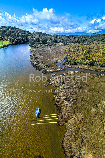 Lone whitebaiter waiting on the Okari River with nets for whitebait fish to become visible swimming over white spotter boards. Tidal Okari Lagoon. Aerial view, Charleston, Buller District, West Coast Region, New Zealand (NZ) stock photo.