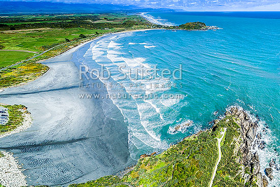 Tauranga Bay Beach, with Cape Foulwind Walkway below right. Aerial view looking south, Cape Foulwind, Buller District, West Coast Region, New Zealand (NZ) stock photo.