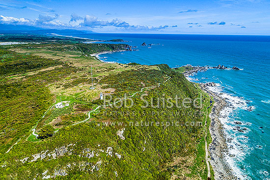 Cape Foulwind Lighthouse and Cape Foulwind Walkway track. Aerial view with Tauranga Bay behind, Cape Foulwind, Buller District, West Coast Region, New Zealand (NZ) stock photo.