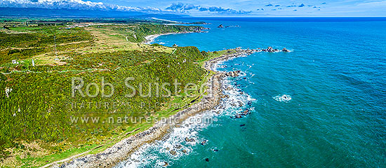 Cape Foulwind. Aerial panorama looking past Cape Foulwind Lighthouse (left) and Cape Foulwind Walkway towards Tauranga Bay and Wall Island (top centre), Cape Foulwind, Buller District, West Coast Region, New Zealand (NZ) stock photo.