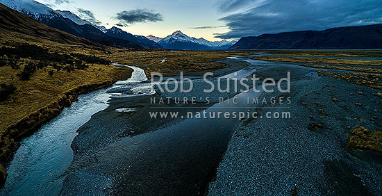 Tasman Valley with braided river channels running down from Aoraki Mt Cook and the Southern Alps. Ben Ohau Range and Freds Stream left. Moody aerial panorama, Aoraki / Mount Cook National Park, MacKenzie District, Canterbury Region, New Zealand (NZ) stock photo.