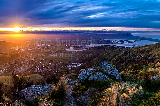 Christchurch City and Canterbury Plains at sunset, from the Port Hills. Avon Heathcote Rivers estuary and Pegasus Bay right, Port Hills, Christchurch, Christchurch City District, Canterbury Region, New Zealand (NZ) stock photo.