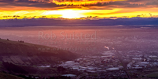 Christchurch City and Canterbury plains on a calm winter evening with fog settling and snow on the Southern Alps beyond. Sunset panorama, Port Hills, Christchurch, Christchurch City District, Canterbury Region, New Zealand (NZ) stock photo.