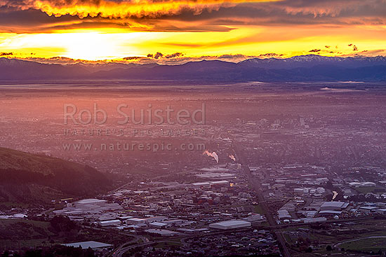 Christchurch City and Canterbury plains on a calm winter evening with fog settling and snow on the Southern Alps beyond. Sunset, Port Hills, Christchurch, Christchurch City District, Canterbury Region, New Zealand (NZ) stock photo.