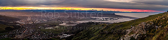 Christchurch City and Canterbury plains on a calm winter evening with snow on the Southern Alps beyond. Heathcote and Avon Estuary, and Pegasus Bay at right. Sunset panorama, Port Hills, Christchurch, Christchurch City District, Canterbury Region, New Zealand (NZ) stock photo.