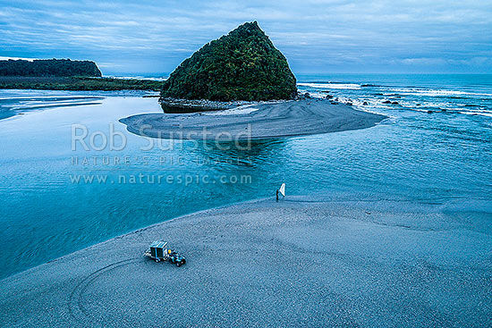Lone whitebaiter scooping whitebait at the Wanganui River mouth at dawn on the rising tide. Mt Oneone headland beyond. Aerial view, Harihari, Westland District, West Coast Region, New Zealand (NZ) stock photo.