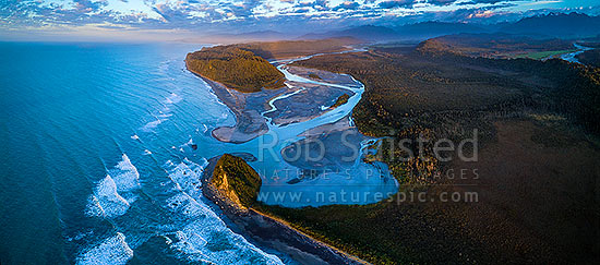 Wanganui Heads, River mouth and tidal lagoon. Mt Oneone (56m) bottom centre, Wanganui Bluff above. Southern Alps beyond, and Poerua River far right. Moody aerial panorama at dusk, Harihari, Westland District, West Coast Region, New Zealand (NZ) stock photo.