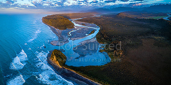 Wanganui Heads, River mouth and tidal lagoon. Mt Oneone (56m) bottom left, Wanganui Bluff above. Southern Alps beyond, and Poerua River far right. Moody aerial panorama at dusk, Harihari, Westland District, West Coast Region, New Zealand (NZ) stock photo.