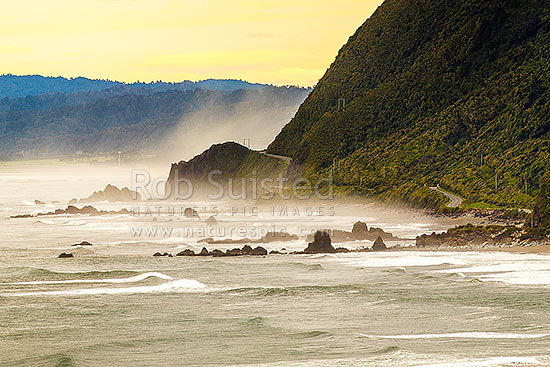 Paparoa Coast Road (State Highway 6 SH6) passing Seventeen Mile Bluff as sea fog rolls in. Barrytown flats at left, Barrytown, Grey District, West Coast Region, New Zealand (NZ) stock photo.