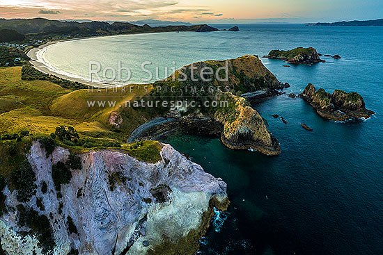 Opito Point Historic Reserve and Opito Bay at twilight. Great Mercury Island top right. Aerial view, Opito Bay, Coromandel Peninsula, Thames-Coromandel District, Waikato Region, New Zealand (NZ) stock photo.