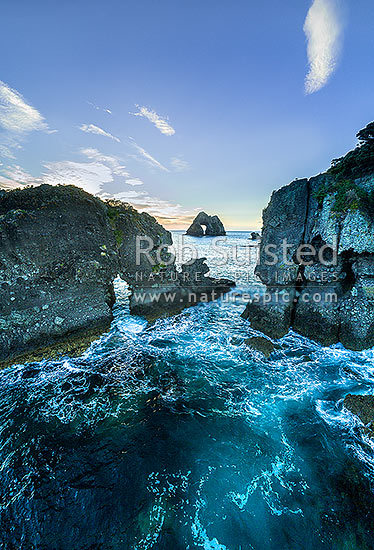 Motukoruenga Island and rocks, with Needle Island behind centre. Hole in the Wall channel, Opito Bay, Coromandel Peninsula, Thames-Coromandel District, Waikato Region, New Zealand (NZ) stock photo.