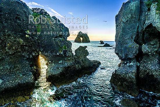 Motukoruenga Island and rocks, with Needle Island behind centre. Hole in the rock in Hole in the Wall channel, Opito Bay, Coromandel Peninsula, Thames-Coromandel District, Waikato Region, New Zealand (NZ) stock photo.
