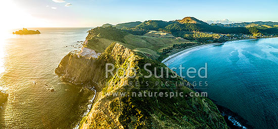 Opito Point Historic Reserve at sunrise, with Motukoruenga Island far left, and Opito Bay and Opito Beach at right. Aerial panorama, Opito Bay, Coromandel Peninsula, Thames-Coromandel District, Waikato Region, New Zealand (NZ) stock photo.
