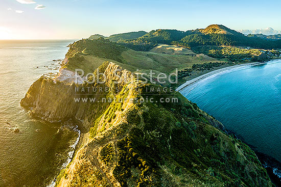 Opito Point Historic Reserve at sunrise with Opito Bay and Opito Beach at right. Aerial view, Opito Bay, Coromandel Peninsula, Thames-Coromandel District, Waikato Region, New Zealand (NZ) stock photo.