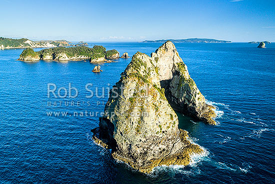 Needle Rock with a hole through the centre of the island, in the Hole in the Wall Channel, with Motukoruenga Island and Opito Point at left, Mercury Islands in distance. Aerial view, Opito Bay, Coromandel Peninsula, Thames-Coromandel District, Waikato Region, New Zealand (NZ) stock photo.
